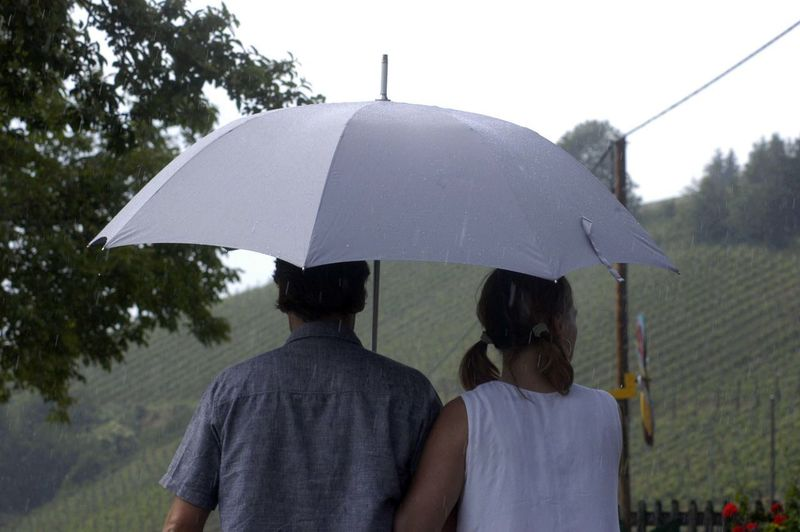 Rear view of people on wet umbrella during rainy season