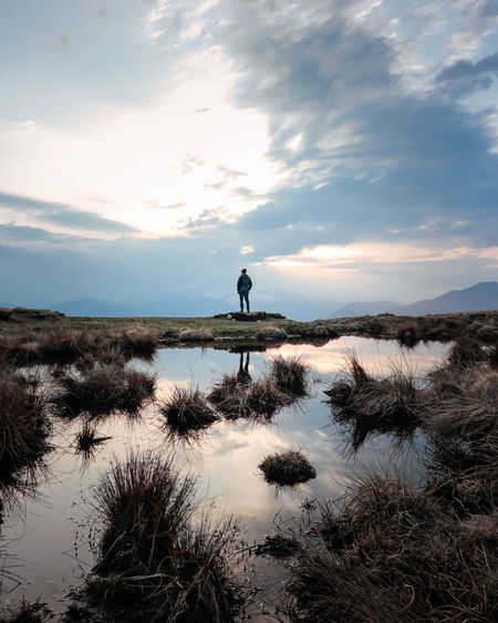 Adventure Back View Beauty In Nature Calm Cloud - Sky Hikingadventures Lake Lonely Mountains And Sky Nature One Person Outdoors Real People Reflections Scenics Silhouette Sky Standing Standing Water Sunset Tranquil Scene Tranquility Wild Lost In The Landscape