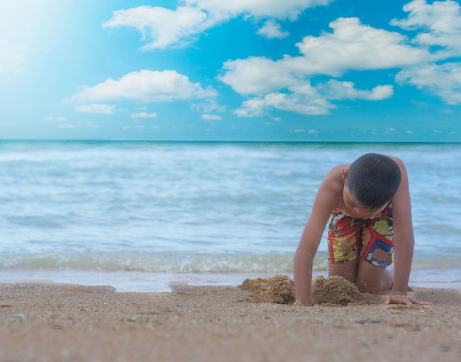 Boy Digging Sand At Beach Against Sky