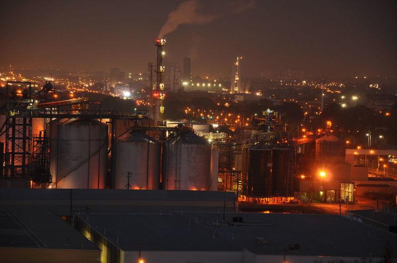 Illuminated factory in city at night