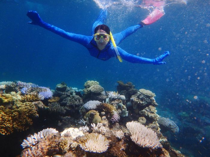Full Length Portrait Of Woman With Arms Outstretched Snorkeling In Sea
