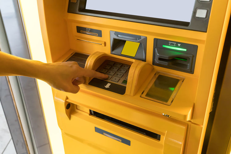 Hand of Asian woman pressing digit buttons on yellow ATM machine. Adult Economy Statement Banking Card Casual Clothing Code Computer Concept Deposit Digital Digits Finger Hand Keypad Money Money Around The World Password People Pin Slip