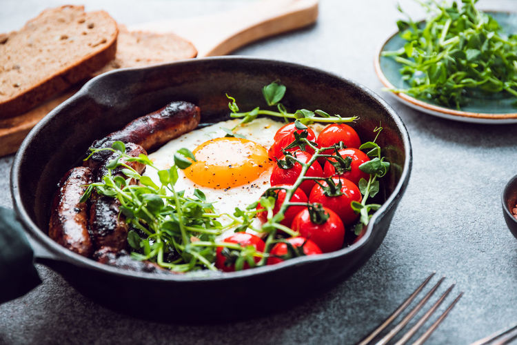 Breakfast time, fried egg with sausages and cherry tomatoes in a black iron pan, served microgreens. Breakfast Time Table Fried Egg Pan English Sausages Cherry Tomatoes Black Microgreens Bread Eating Food Morning Bacon Toast Omelet Dish Background Vegetable Meal Fry Tasty Cooking American Roasted Yolk Traditional Homemade Food And Drink