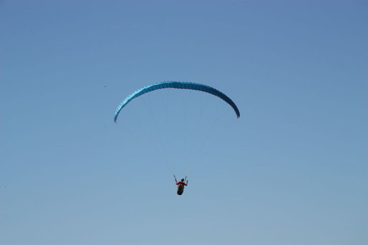 Low angle view of man paragliding against clear blue sky