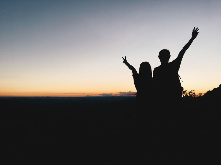 Arms Raised Day Gesturing Horn Sign Human Hand Leisure Activity Lifestyles Men Nature Outdoors People Real People Silhouette Sky Sunset Togetherness