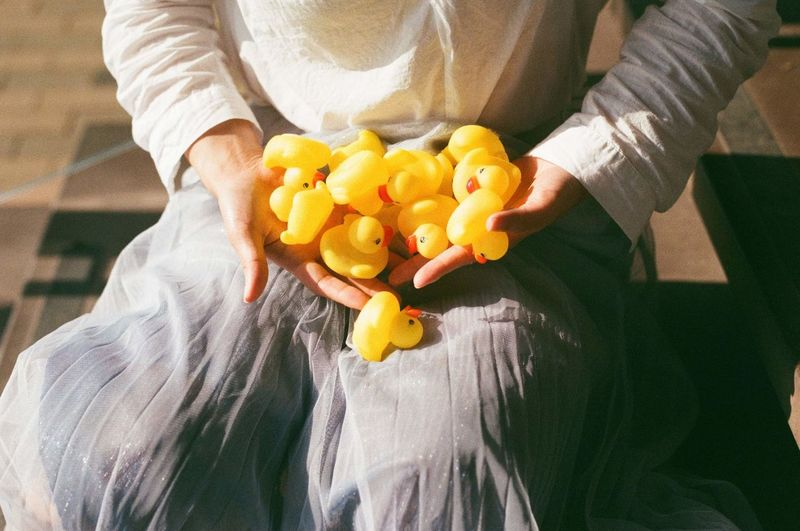 Midsection of woman holding rubber ducks while sitting on steps