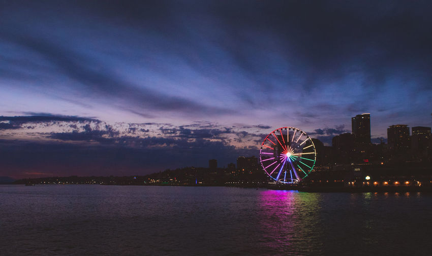 Illuminated ferris wheel by sea against sky at night