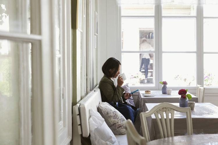 Woman sitting on window at home