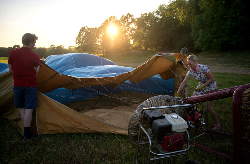 People adjusting tent on field against trees