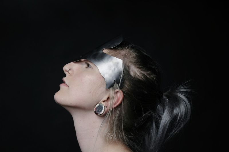 Profile view of young woman wearing headdress against black background