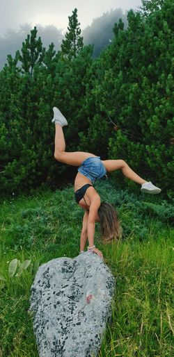 Woman doing handstand on rock against plants