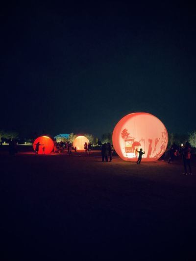 People at illuminated park against sky at night