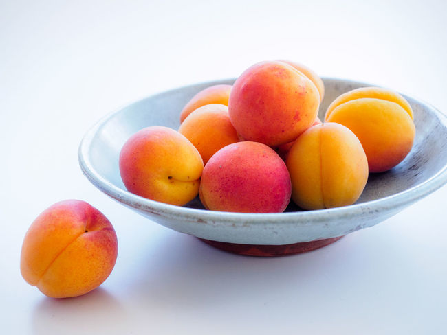 Apricots in a Bowl on a White Table Apricots Summer Fruits Close-up Food Freshness Fruit Healthy Eating Organic Fruits