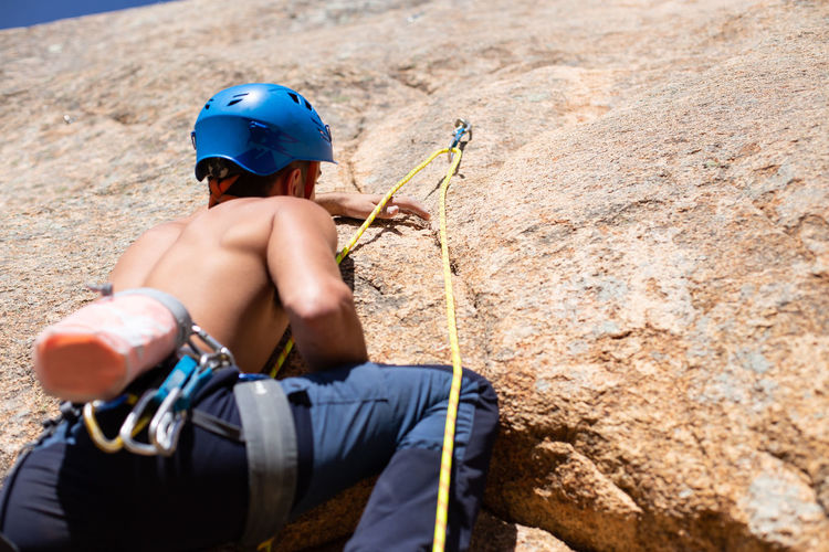 Close up of shirtless male climber climbing mountain wall on amazing sunny day Man Climbing Climber Rock Cliff Sunny Daytime Shirtless Sport Mountain Extreme Sports Activity Height Rope Challenge Strong Adventure RISK Exercising Grip Young Adult Fearless Athlete Training Outdoors