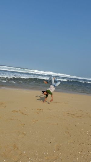 Mid adult man doing handstand at beach against clear blue sky during sunny day