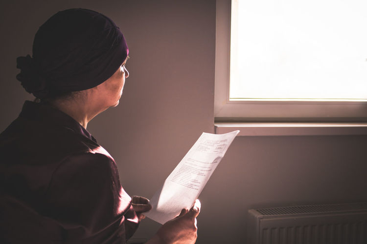 Side view of woman reading medical letter at window