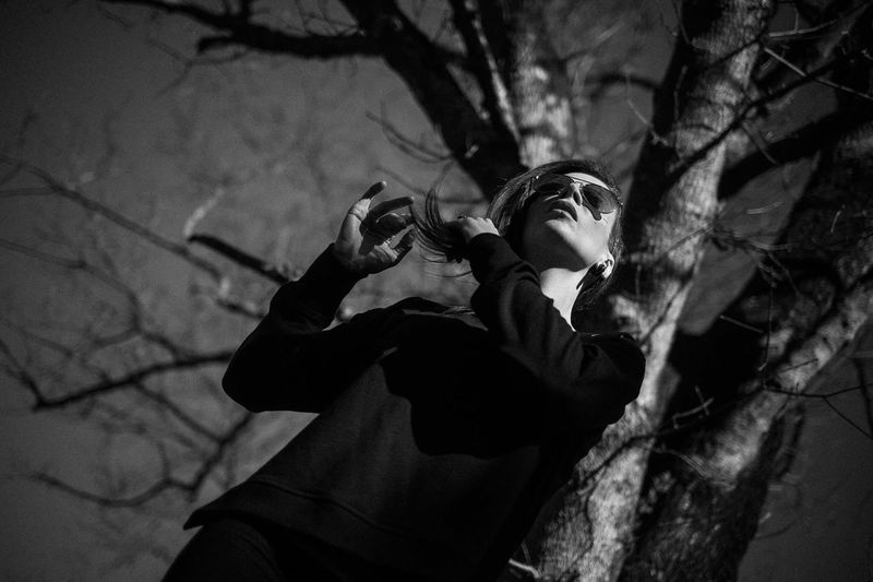 Low angle view of woman standing against bare tree