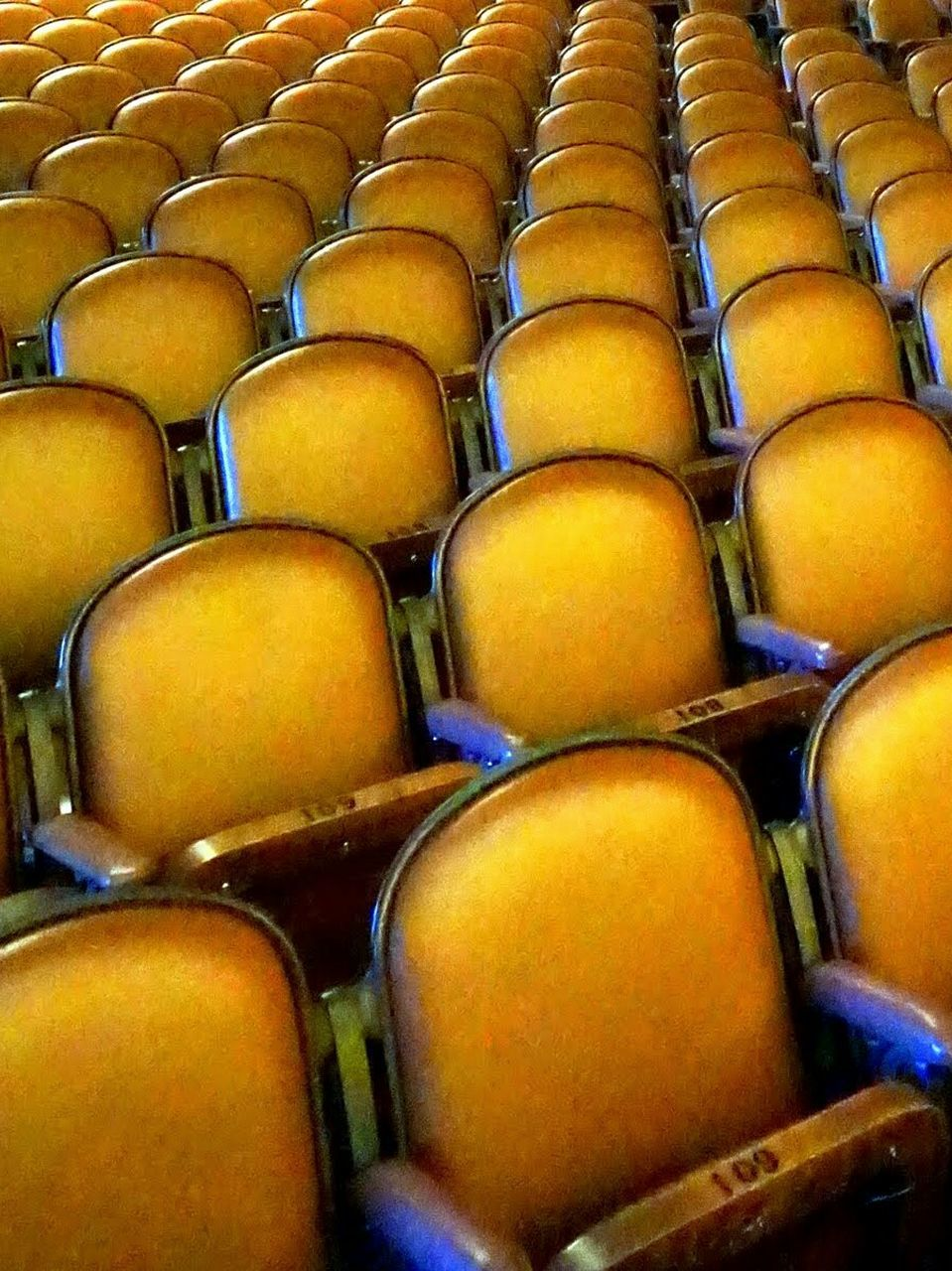 in a row, full frame, seat, abundance, indoors, large group of objects, auditorium, arrangement, backgrounds, no people, day