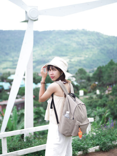 Young woman wearing hat standing against landscape