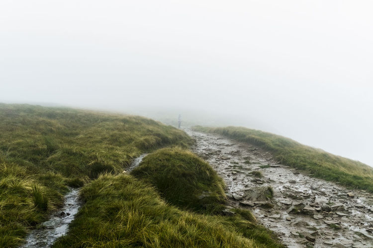 Scenic View Of Path On Grassy Hill In Foggy Weather