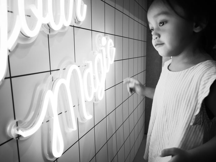 Side view of girl looking at illuminated lamp