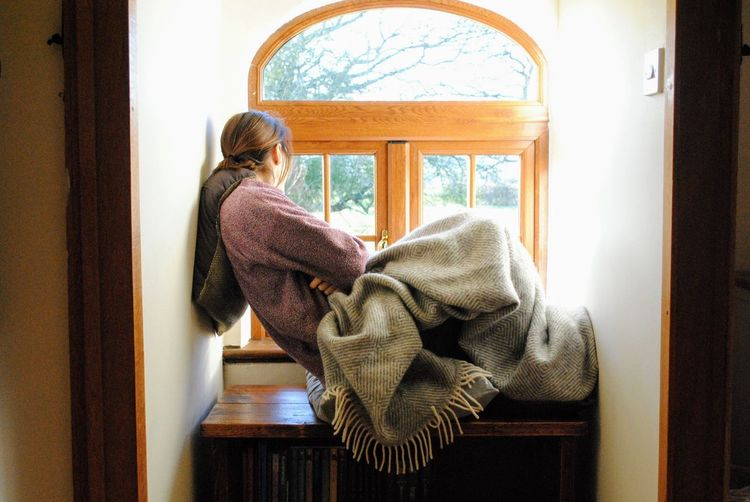 Woman sitting on window seat at home
