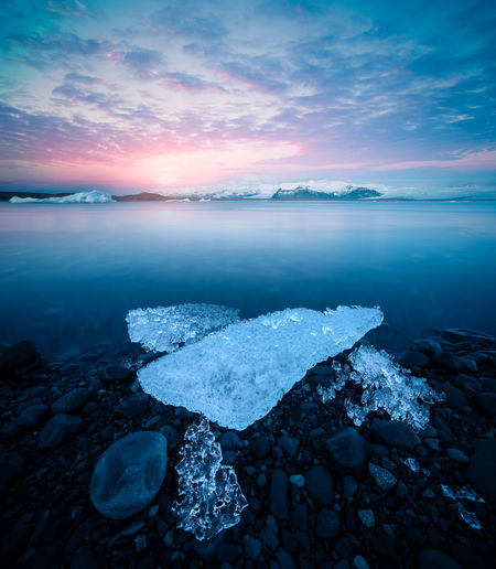 Beautiful scenic view of jokulsarlon glacier at sunset with ice chunks and mountains.