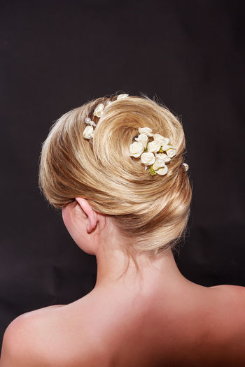 View from behind of a stylish woman with an elegant blond hairstyle with her hair swept up into a neat bun secured with a floral hair accessory and bare shoulders Back Hair Sophisticated Accessories Black Background Blond Hair Close-up Flower Glamourous Hair Fashion Hairstyle Headshot Indoors  Juwelry Maintained Neck Node People Rear Rolê Studio Shot Style Wedding Hair Wedding Hairstyles Women