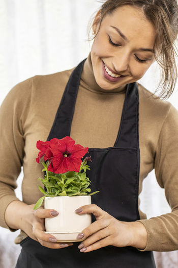 Close-up of smiling young woman holding red rose