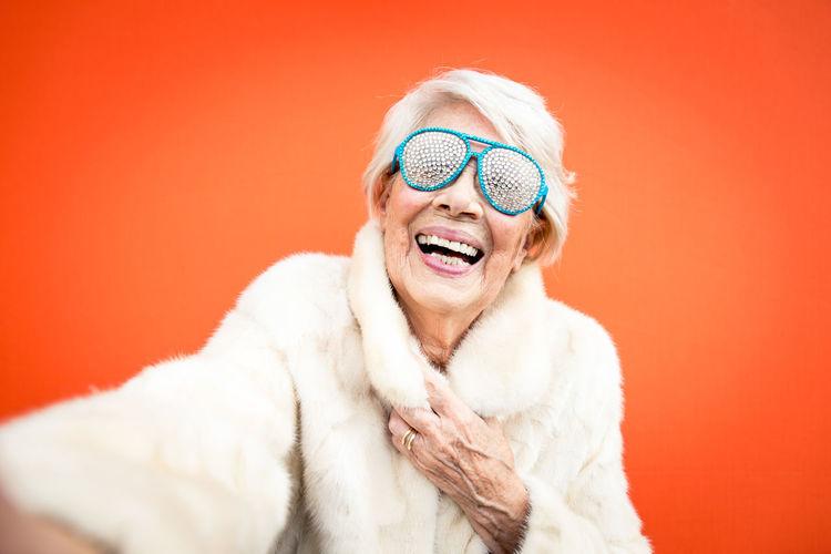 Portrait of cheerful senior woman wearing sunglasses against orange background