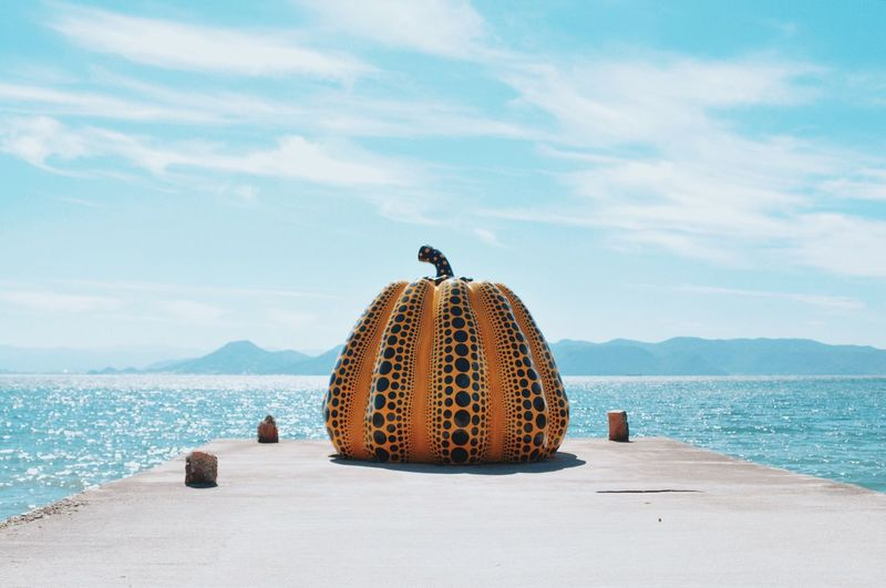 Pumpkin decoration of pier at beach against sky