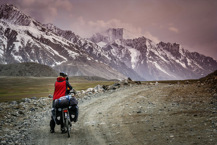 Rear view of woman with bicycle leading towards snowcapped mountain against sky