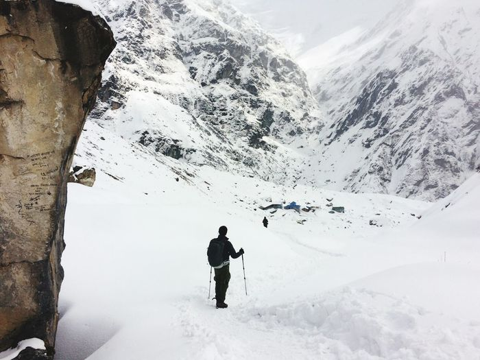 Rear view of man holding ski poles standing on snow covered field