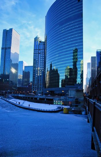 View of reflective buildings behind a frozen Chicago River on a frigid morning in early January. Chicago Chicago River Cityscape Downtown Chicago Architecture Blue Building Exterior Building Exterior Architecture Built Structure City Cityscape Day Downtown District Financial District  Modern No People Office Park Outdoors Road Sky Skyscraper Tall Tower Travel Destinations Urban Skyline Shades Of Winter