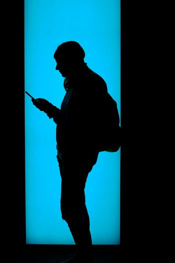 Side view of silhouette man using smart phone against blue background