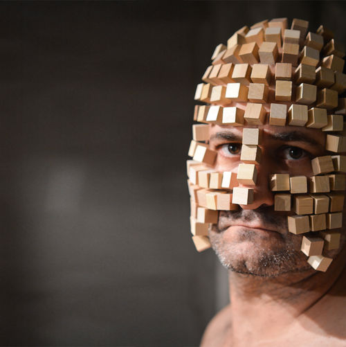 Close Up Of Man With Wooden Blocks On Face