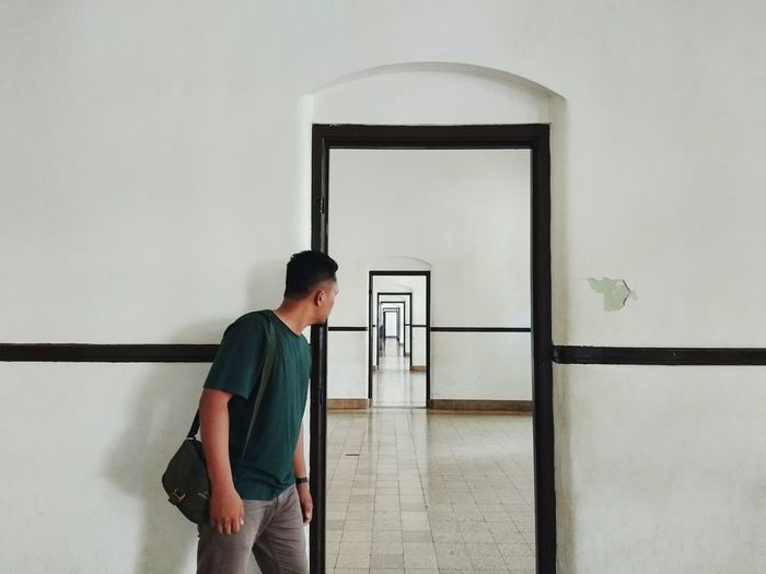 Young man looking at corridor through door