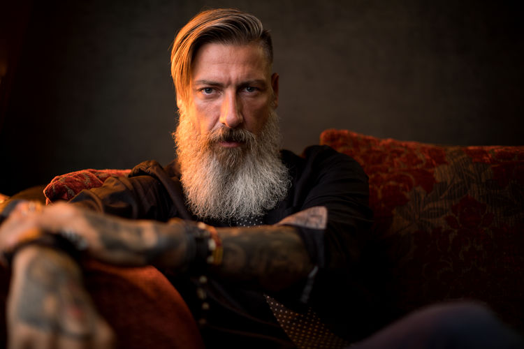 Portrait of an attractive modern business man in front of a dark background Light Tattooed Adult Beard Bearded Businessman Clothing Club Confident  Contemplation Furniture Hipster Lifestyles Males  Mature Men Men Millionnaire One Person Portrait Relaxation Rocker Sitting Sofa Studio Shot Tattoo