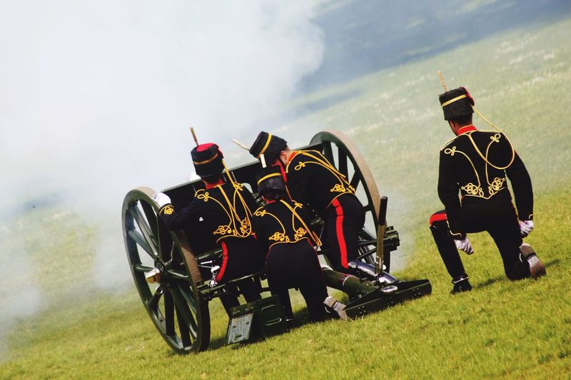 Rear View Of Army Soldiers With Metallic Wheels On Grassy Field