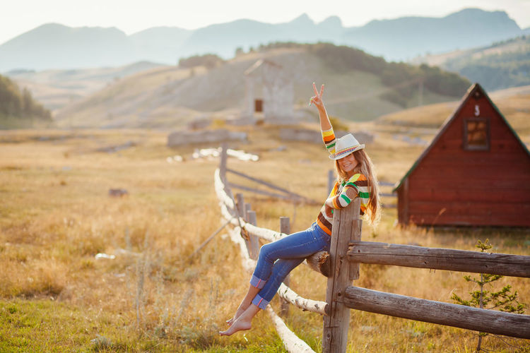 woman travel at countryside village. Cowgirl relax outdoors at field. EyeEm Best Shots Fashion Field Jeans Travel Traveling Casual Clothing Countryside Cowgirl Day Grass Hat, Lifestyles Mountain Mountain Range Nature One Person Outdoor Outdoors People Real People Relax Sky Village Young Adult