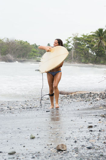 Woman with surfboard walking at beach