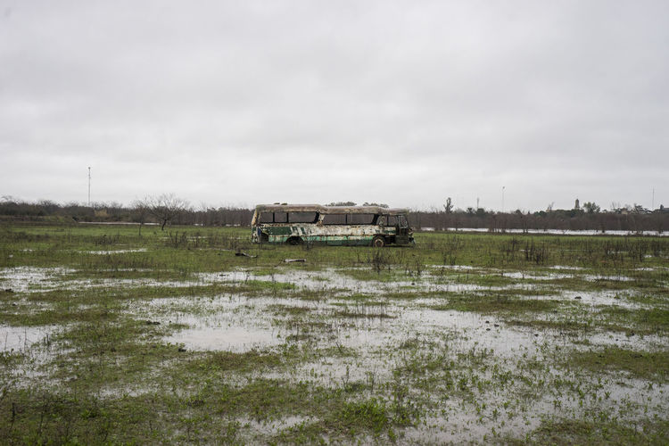 Abandoned Bus in Field Abandoned Building Bus Couldy Greast Horizon Marsh Overcast Rain Rundown Rust Swamp Transportation Wet