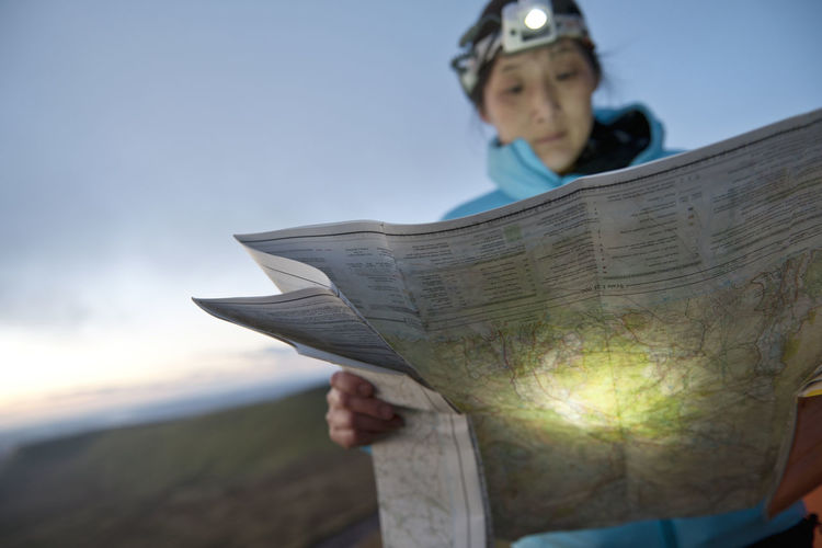 Full length of a boy holding book against sky