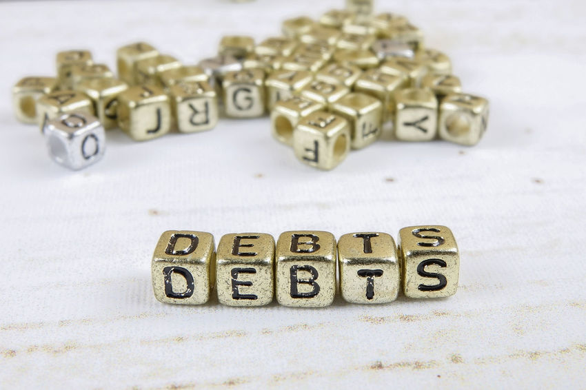 DEBT CONCEPT WITH GOLD DICE ON A WOODEN TABLE Alphabet Capital Letter Close-up Communication Credit Card Debt Crisis High Angle View Indoors  Large Group Of Objects Letter No People Number Selective Focus Still Life Studio Shot Table Text Toy Toy Block Western Script White Background