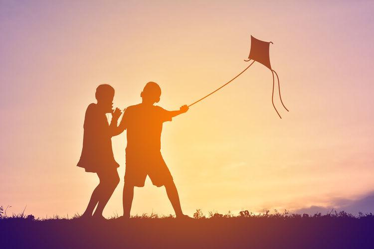 Silhouette Of Children Flying Kite