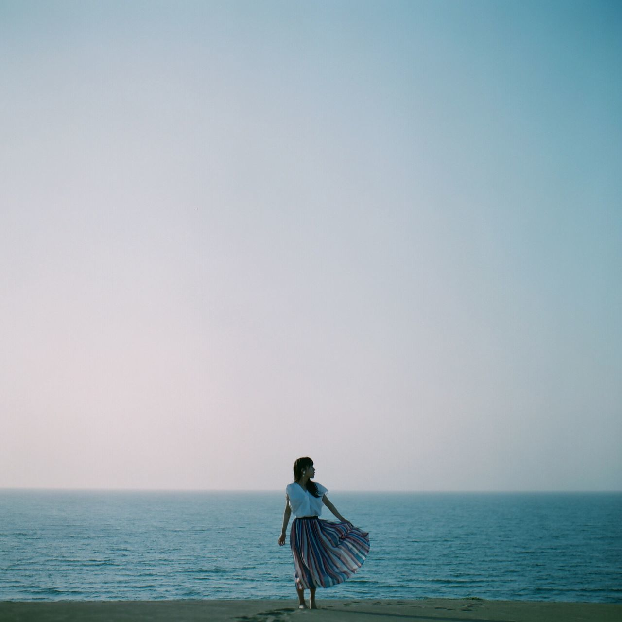 sea, horizon over water, water, clear sky, tranquil scene, scenics, copy space, beauty in nature, nature, tranquility, one person, real people, sky, beach, standing, outdoors, day, lifestyles, young adult, young women, people