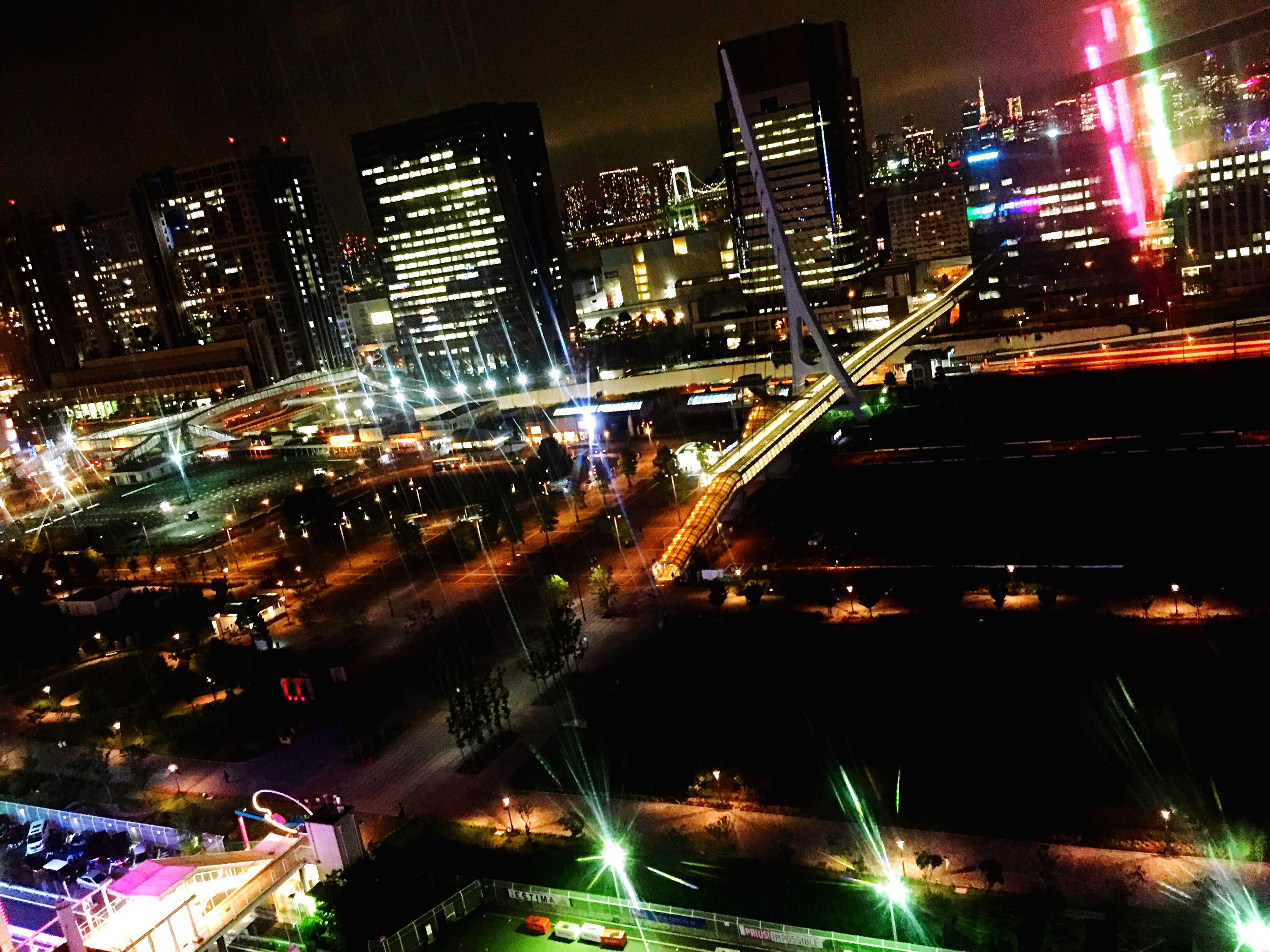 illuminated, night, city, architecture, building exterior, built structure, cityscape, city life, skyscraper, modern, outdoors, travel destinations, no people, road, transportation, motion, urban skyline, high street, sky
