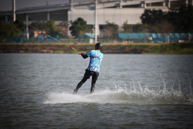 Rear view of man waterskiing in sea