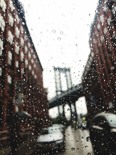 City seen through wet glass window during rainy season