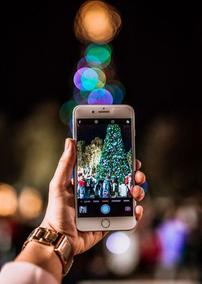Close-up of hand holding smart phone at night